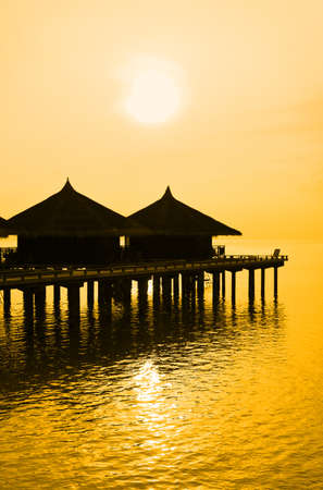 Water bungalows and sunset - abstract vacation background photo