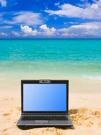 Computer notebook on beach - business travel background photo