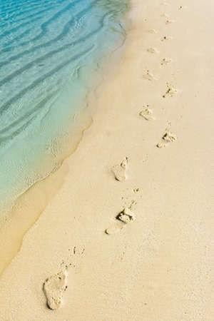 trailway: Foot steps and surf on tropical beach - abstract travel background