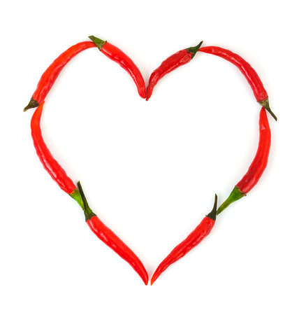 Heart made of red hot chili pepper isolated on white background photo