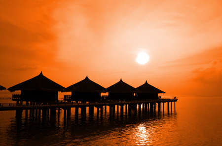 Sunset and water bungalows, abstract vacation background photo