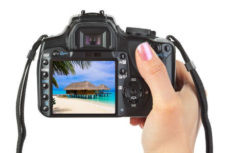 Camera in hand and beach landscape (my photo) isolated on white background