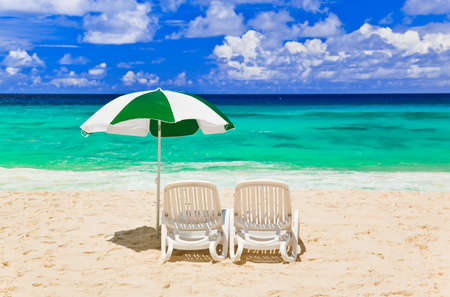Chairs and umbrella at tropical beach - vacations background photo