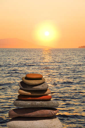 stacking: Stack of stones on beach at sunset - nature background Stock Photo