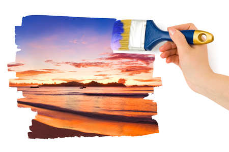 Hand with paintbrush painting sunset isolated on white background photo