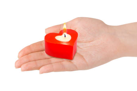 Heart shaped candle in hand isolated on white background photo
