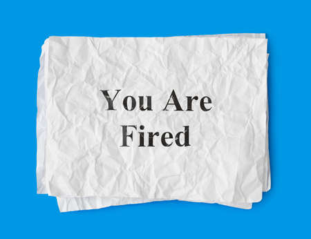 Paper You Are Fired isolated on blue background photo
