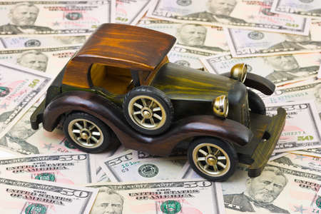 Toy retro car on money background - business concept photo