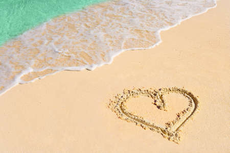 sand drawing: Drawing heart on beach - love concept