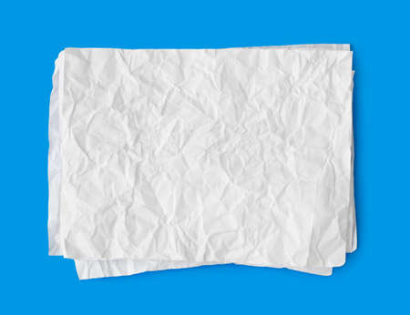 Crumpled paper stack isolated on blue background photo