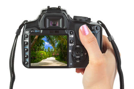 Camera in hand and beach landscape (my photo) isolated on white background photo