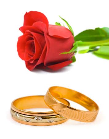 Rose and wedding rings isolated on white background photo