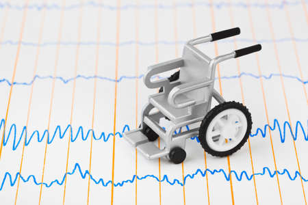 Toy wheelchair on ecg - medical background Stock Photo - 9594257