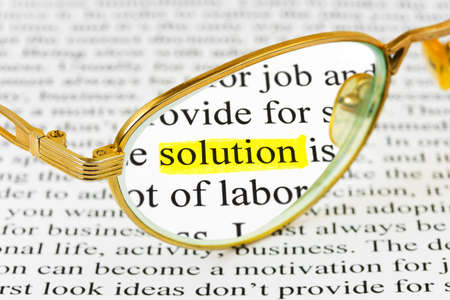 Glasses on business article and word solution Stock Photo - 9640653