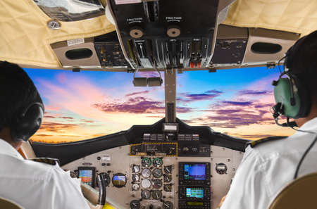 pilot cockpit: Pilots in the plane cockpit and sunset Stock Photo