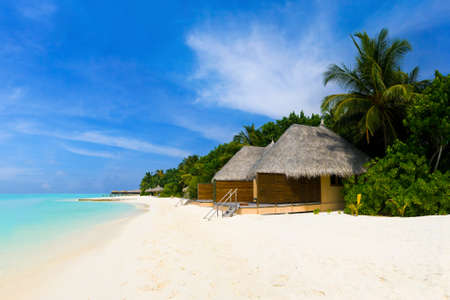 Tropical beach and bungalows - travel vacation background photo