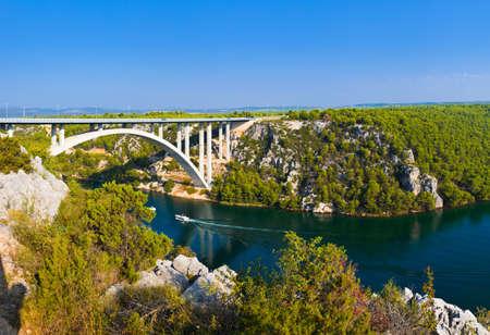 waterfall in the city: River Krka and bridge in Croatia - travel background