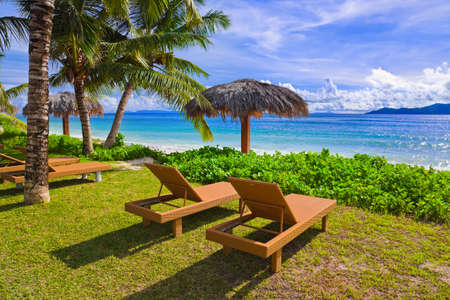 sun umbrellas: Chairs on tropical beach at Seychelles - vacation background