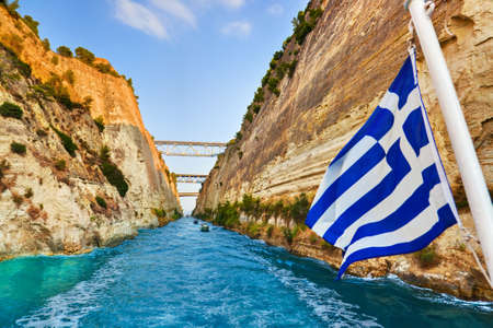 isthmus: Corinth channel in Greece and greek flag on ship - travel background