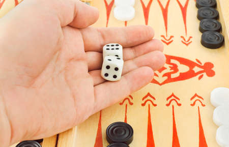 Hand with dices and backgammon game photo