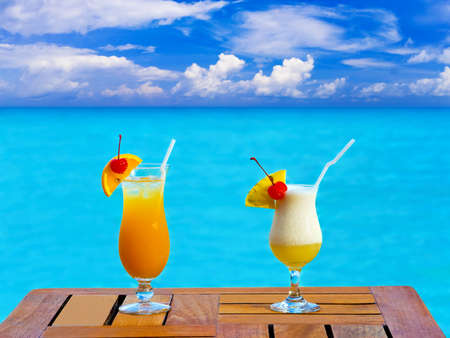 Two cocktails on table, sea background photo