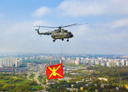 Helicopter with military flag over Moscow at parade of victory day - aerial view photo