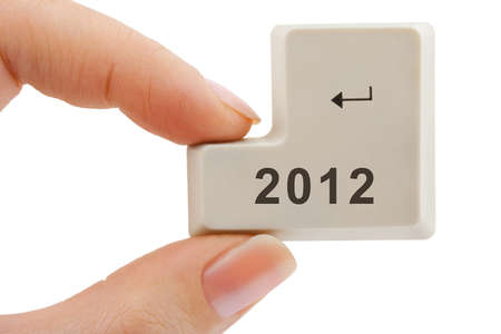 Computer button 2012 in hand isolated on white background photo