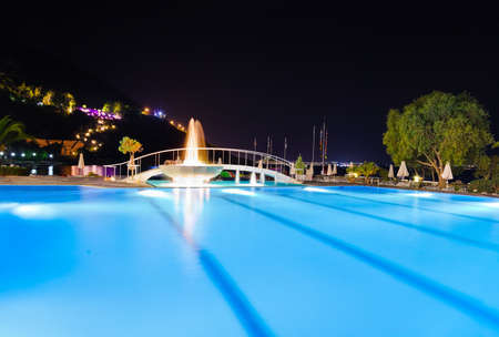 Water pool and fountain at night - vacation background photo