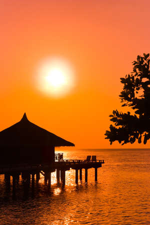 caribbean climate: Water bungalows and sunset - abstract vacation background