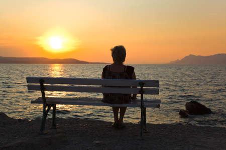 despedida: Mujer en el banco y el atardecer - fondo de vacaciones