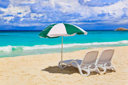 the chaise lounge: Chairs and umbrella at tropical beach - vacations background