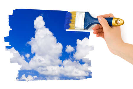 Hand with paintbrush painting sky isolated on white background photo