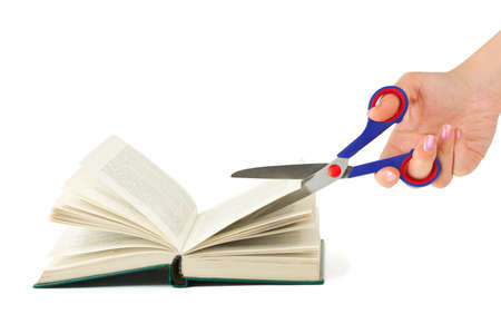 scissors cutting paper: Hand with scissors cutting book isolated on white background Stock Photo