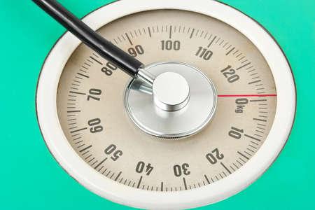 Stethoscope on weight scale - medical background photo