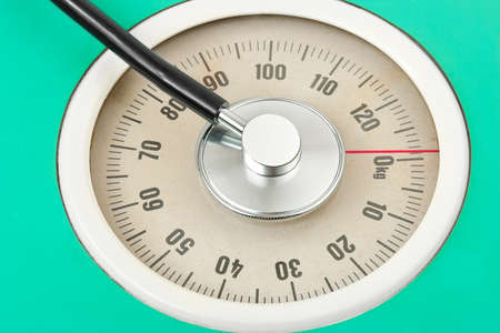 kg: Stethoscope on weight scale - medical background Stock Photo