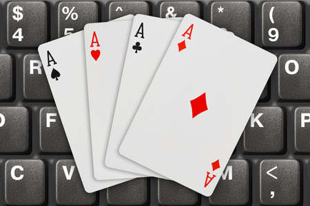 Playing cards on computer keyboard - internet games concept photo