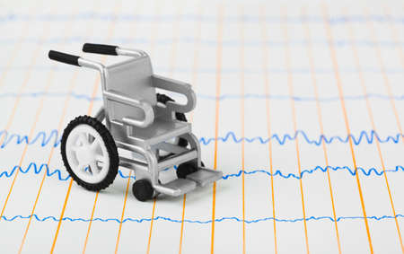 Toy wheelchair on ecg - medical background photo