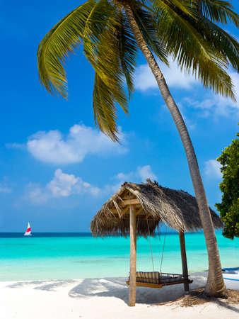 Swing op een tropisch strand - vakantie symbool Stockfoto