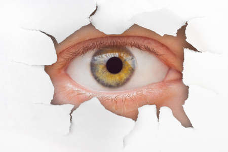 Eye looking through hole on paper surface photo