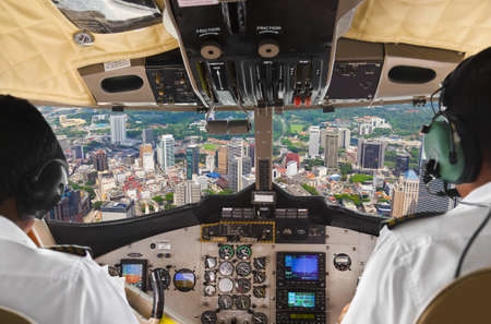 airplane landing: Pilots in the plane cockpit and town