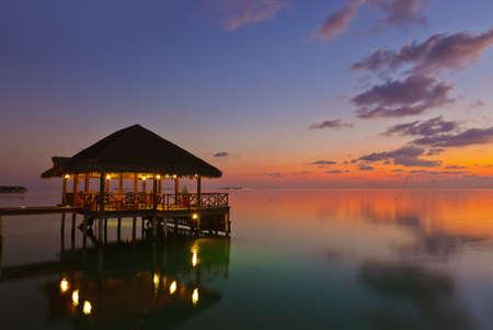 Water Cafe bei Sonnenuntergang - Malediven Urlaub Hintergrund