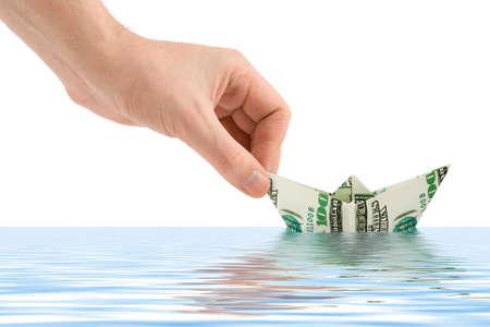schuld: Hand de lancering van geld het schip op een witte achtergrond Stockfoto