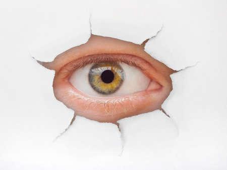 broken through: Eye looking through hole on paper surface