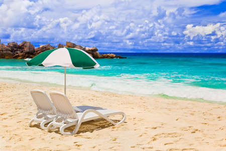 beach chairs: Chairs and umbrella at tropical beach - vacations background