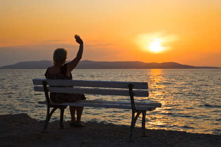 farewell: Woman on bench and sunset - vacation background