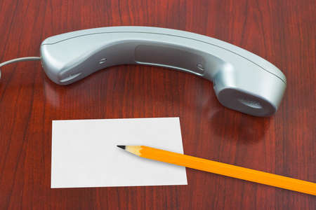 telephone receiver: Phone, paper card and pencil on wooden table