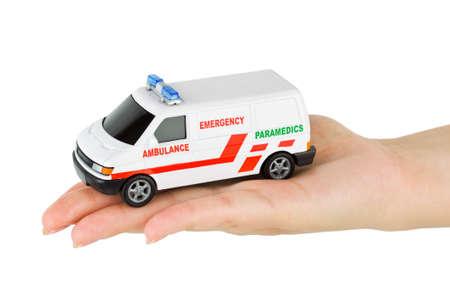 Hand with toy ambulance car isolated on white background photo