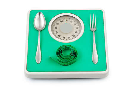 Fork and spoon on weight scale isolated on white background photo
