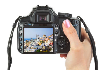 Camera in hand and Santorini view  my photo  isolated on white background photo