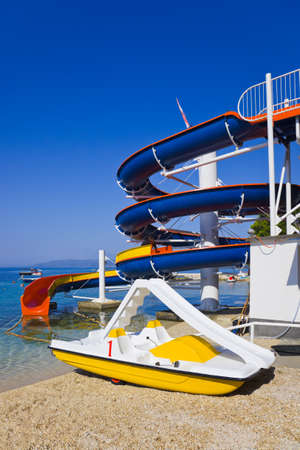 Waterslide and catamaran on beach - vacations background photo